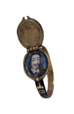 Finger-ring; gold; shoulders with scrolls reserved on ground of black enamel; oval bezel opening as locket, containing enamelled portrait of Charles I with blue ground; lid has table diamond in square setting on ground with scrolls on black enamel; edges and back of bezel are also enamelled in black. 17th century. British Museum