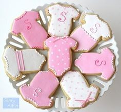 Customized cookies in a dainty baby onesie shape decorated to announce the arrival.