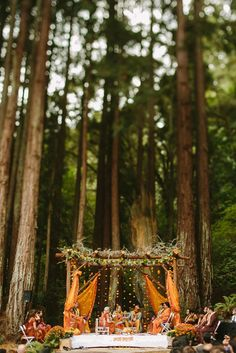 Stunning orange summer drapes with floral hangings in a rustic mandap. Forest wedding at its best!