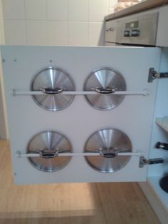 Gordijnroetjes aan de binnenkant van een keukenkastje geschroefd. Pannendeksels ertussen. Blijven hangen aan de handgreep.