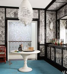 A dramatic Piero Fornasetti cloud-pattern wallpaper by Cole & Son panels the wet bar | archdigest.com