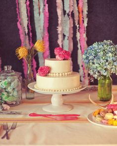 This two-tier vanilla cake, covered with buttercream frosting and garden roses, sat on an antique pedestal at this wedding in Marfa, Texas. It was framed by vases of pincushion proteas and hydrangeas.