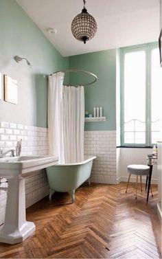 salle de bain rétro avec parquet massif et murs en blanc et turquoise
