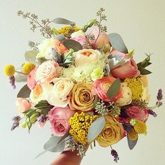 Fun and bright mixed bouquet of yarrow, ranunculus, and billy balls