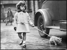 Little Girl walking her Cat. Photograph.