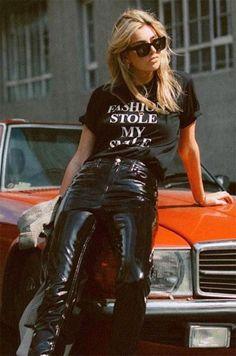 Camille Charrère usa calça de vinil, camiseta preta e óculos wayfarer.
