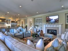 Coastal decor is found in the details in this spacious family room. Upholstered light-sea blue chairs sit aside an off-white sectional sofa and additional seating is provided by upholstered ottomans. A large flat-panel television hangs above a grand fireplace. Custom cabinetry provides additional storage for this open concept living room.