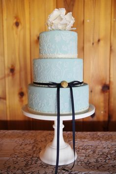 Pale blue cake with white flower. Not big on the bow but I like the detail