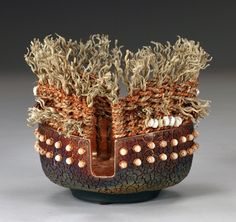 """Raku pottery by Marc Jenesel and basketry by Karen Pierce. Raku pottery lined with copper leaf (2 slots, altered rim), rattan, dyed seagrass, copper wire, beads, sea shells. 7.5""""h x 6.5"""" dia."""