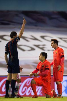 Referee Inaki Vicandi Garrido shows a yellow card to Luis Suarez (C) of FC Barcelona during the La Liga match between Celta Vigo and FC Barcelona at Estadio Balaidos on April 5, 2015 in Vigo, Spain.