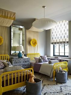 I like the design principles of this room...brightly colored bed frames, wide variety of texture and pattern, mixture of classic elements with modern and ethnic, and the canopies.