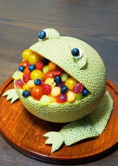 A melon has been made into a frog with it's mouth filled with lots of colourful fruit. It can be used as a table display to tempt children to eat fruit. #healthy
