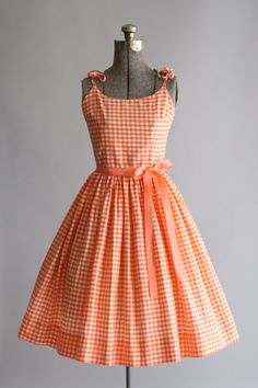 This 1950s cotton dress features a orange and white gingham print. Double spaghetti straps which tie at the shoulders. Full pleated skirt. Metal zipper up back of dress. Includes a ribbon waist tie. Very good vintage condition. Please note: petticoat worn under skirt for added volume. This piece has been cleaned and is ready to wear!    Label Boyds  Fabric Cotton  Estimated Size XS  Tag Size 12  Pit to Pit 16  Waist 11.5  Hips Open  Shoulder -  Sleeve -  Length 38  Color Orange/White