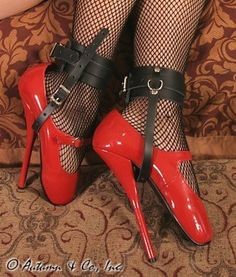 "751T-BLK Buckling Ankle & Shoe Cuffs, Black Leather   These are simply a lovely pair of shoe cuffs to keep those lovely shoes or boots on your slave's feet!  The 2"" ankle cuff buckles tightly and the 1/2"" strap goes under the shoe in front of the heel. These buckles don't have locking tongues, but you can still put padlocks through the regular buckle holes in the strap which would make removing these cuffs and the high heels impossible without the keys!  Use a double snap hook to attach both…"