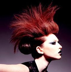 A long red straight spikey coloured crimped spikey bun avant garde hairstyle by Halo