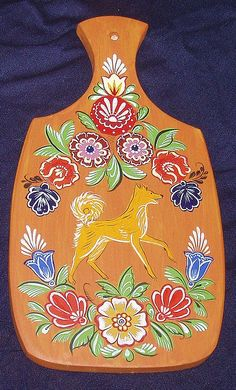A wooden chopping board decorated with folk Gorodets painting from Russia. #art…