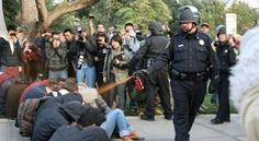 A police officer pepper-sprays Occupy protesters at the University of California [2011]