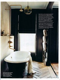 Always loved this for a master bath. The black works on the walls so well because of the great amount of natural light. I love the towel rack and the herringbone wood floor.