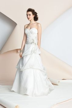 Strapless sweetheart draped cross-over bodice has a skirt with soft pickups and a delicate crystal applique accents the waistline.