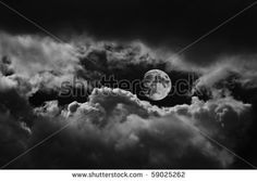 Moon between the clouds in black and white - stock photo