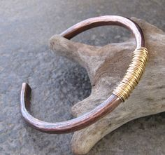 This is a rugged, rough cuff bracelet for a rugged man. I made this from super thick, 4g copper wire. It is 1/4 thick. I hammered it out on a piece of old rust pitted steel to give it the texture and then shaped into an oval. I oxidized it then I wrapped the center section in 12K