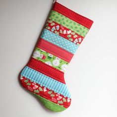 This beautiful quilted stocking has been crafted from 100% cotton designer prints. It has been strip pieced and then quilted by machine. It is fully lined and has been quilted/padded with 100% cotton batting. It is a quality item that could become an heirloom. The stocking back is a red and white dot and it is lined in a creamy white Moda Bella cotton. The stocking has a coordinating fabric loop for hanging. The toe on this stocking points to the right. All my items are expertly sewn with…
