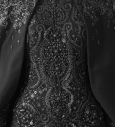 Black dress detail with intricate embellishments; couture embroidery; close up fashion // Alexander McQueen