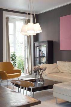 KONTAKT MED UTELIVET: Det er ikke direkte utgang, men når gardinene er trukket fra, har man god kontakt med den frodige gatestubben utenfor. Den gule lenestolen og det rosa veggmaleriet er kjærkomne fargeinnslag i et ellers rolig ton-i-ton-regime. Taklampen er kjøpt på Raun, skapet er fra Home og Cottage.