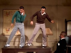 Donald O'Connor and Gene Kelly dancing on the table in Singin' In the Rain.