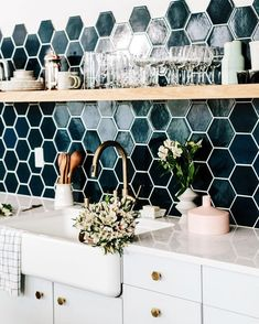 The dark geometric backsplash creates a striking and refreshing contrast to the gleaming white kitchen units.