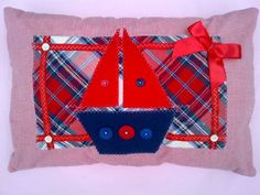 A 45 x 30cms cushion, handcrafted from an upcycled red check shirt, the cushions being the opening at the back. Appliqued with a boat and decorated with a a satin ribbon and bow and buttons.