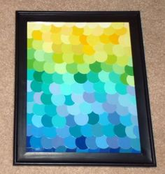 Decoupaged multi-colored circles cut from paint chips and framed to create inexpensive art