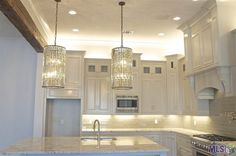 | Light Granite Coutners | Unique Light Fixtures | Lighting above Cabinets | White Cabinets | Light Backsplash | Recessed Lighting Under Cabinets | Stainless Steel Appliances | Kitchen Island | Light Paint Color to Reflect Light |