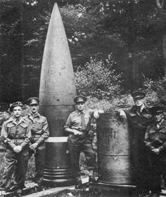 """British Army officers pose next to projectiles fired by the """"Dora"""" railway gun. Dora and its sibling """"Gustav"""" were 80 cm guns developed in the late 1930s by Krupp as siege artillery for the purpose of destroying the French Maginot Line fortifications. The guns could fire shells weighing seven tonnes to a range of 47 km (29 mi). Gustav was captured by US troops and cut up, whilst Dora was destroyed near the end of the war in 1945 to avoid capture by the Red Army."""