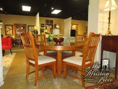 """Round oak dining table in a warm medium finish with four ladderback chairs. The chairs have wheat colored seat. Nice & neutral set! One small door provides storage at the base. 50""""round; 14""""leaf."""