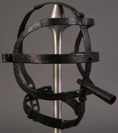 A rare 17th century torture mask with a cage of hinged straps locking at the back of the collar and incorporating a mouth pipe.