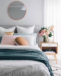 Pillow construction under round mirror in bedroom design