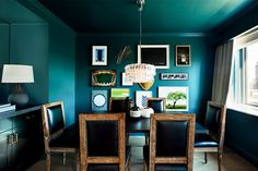 Teal walls in dining space with black and wood chairs and small gallery wall