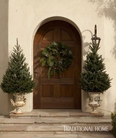 An arched front door and fresh greenery welcomes guests. - Photo: Colleen Duffley