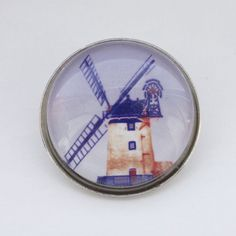 Blue and Red Windmill brooch Photo art by MyriadLifePhotoArt Handmade using a glass cabochon and silver colour metal base.Measures 25mm circumference.Also available as stud and clip earrings and check out the blue windmill cufflinks too!This brooc...