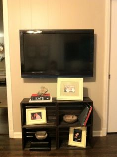 Stain or paint wood crates, then attach to each other to go under the TV- I'm thinking they'd be even nicer attached to the wall (under a higher-mounted TV)!