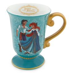 New. The mug is tulip shaped and features Ariel and Prince Eric from Disney's The Little Mermaid. The handle and trims are Golden filigree. Golden Disney Fairytale Disigner Collection logo inside lip. Ceramic. 12 oz. size.