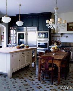 Love the cement/encaustic tile floors.  Dark kitchen cabinets and light cabinets, appliances and table.