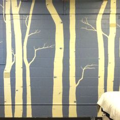 We had this huge cream, cinder block wall that needed some personality. I drew aspen trees (free hand, referencing a few different pictures- sounds more difficult than it turns out to be). I was sure to incorporate exposed pipes and outlet covers into the tree bark so they weren't floating oddly. We taped the corners of the walls, but did not tape around the trees bc it would take FOREVER! :) Use a light hand in edging the trees and it's easy to correct with a little water or an extra coat…