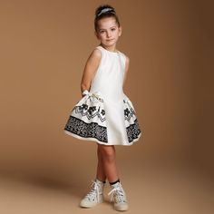 Girls elegant ivory dress with black stitching by ValMax. With a fitted sleeveless bodice, this eye-catching design has a lurex threaded fabric and a puff skirt with an overlay of organza that features detailed cross-stitching in black. It fastens at the back with a zip and has a bow at the front and back and is fully lined for comfort.