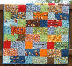 Bright Baby Boy Quilt via Etsy.  I love the fabric used.  Have lots of this fabric myself.  I should make these for the boys beds.