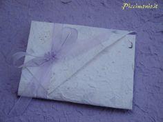 Una partecipazione origami che sorprende per i suoi dettagli, realizzata con carta di gelso arricchita da minuscoli petali e ramoscelli