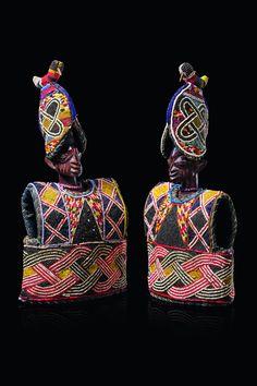 """Male and female twin figure """"ere ibeji"""" in beaded cape """"ewu ileke"""" and hat"""