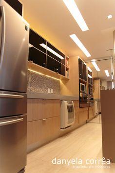 Cozinha integrada com geladeira em inox, forno embutido, armários superiores com vidro preto, pastilhas coloridas na parede, piso de porcelanato, armário inferior com mdf amadeirado. Arquiteta Danyela Corrêa
