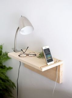 a minimalist wooden plank floating nightstand for holding just a couple of things and charging your phone